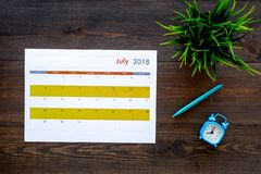 Calendar planner near pen on dark wooden background top view royalty free stock photography