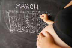 Calendar of the pregnant woman the month March counting days with a calendar for the birth of a child on a chalkboard. The concept. The calendar of the pregnant Stock Image