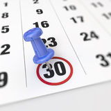 Calendar and pushpin. Calendar and blue pushpin. Mark on the calendar at 30 Stock Image