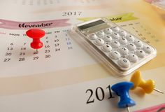 Calendar with red pin and calculator for planning Royalty Free Stock Images