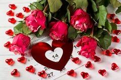Calendar sidan med de röda hjärtorna och buketten av röda rosor på valentindag Royaltyfria Foton