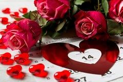 Calendar sidan med de röda hjärtorna och buketten av röda rosor på valentindag Royaltyfri Fotografi