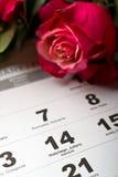 Calendar sidan med de röda hjärtorna och buketten av röda rosor på valentindag Arkivbilder