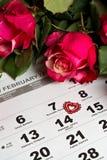Calendar sidan med de röda hjärtorna och buketten av röda rosor på valentindag Arkivfoto