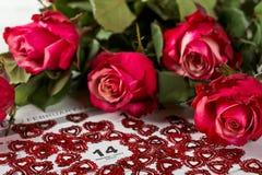 Calendar sidan med de röda hjärtorna och buketten av röda rosor på valentindag Royaltyfri Bild