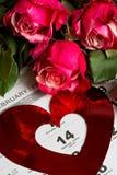 Calendar sidan med de röda hjärtorna och buketten av röda rosor på valentindag Arkivfoton