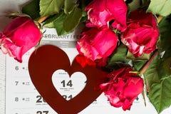 Calendar sidan med de röda hjärtorna och buketten av röda rosor på valentindag Arkivbild