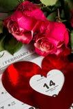 Calendar sidan med de röda hjärtorna och buketten av röda rosor på valentindag Fotografering för Bildbyråer