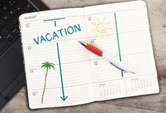 Calendar on table with word VACATION and sun icon against wooden table. Top view of calendar on table with word VACATION and sun icon against wooden table stock photos