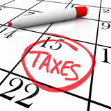 Calendar - Tax Day Circled. The big Tax Day, the 15th, is circled on a white calendar with a red marker Stock Image
