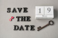 Calendar, vintage key and phrase SAVE THE DATE composed with letters on grey background stock image