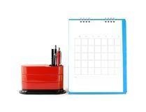 Calendario azul en blanco con el organizador rojo del escritorio en el fondo blanco Fotografía de archivo