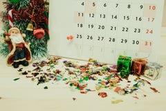 Calendario con el equipo de la decoración del día de la Navidad colocado en woode Imágenes de archivo libres de regalías