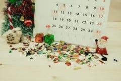 Calendario con el equipo de la decoración del día de la Navidad colocado en woode Imagen de archivo