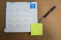 calendario 2017 con mofa encima del post-it y de la pluma para tomar el mensaje Imagenes de archivo