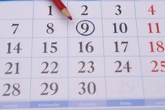Calendario con un lápiz rojo y con el círculo negro Foto de archivo