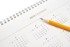 Calendario da scrivania e matita gialla su fondo bianco immagine stock libera da diritti