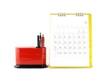 Calendario de escritorio amarillo con días y fechas en julio de 2016 y organizador rojo del escritorio en el fondo blanco Foto de archivo
