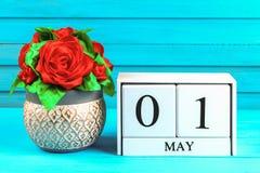 Calendario de madera blanco con el texto: 1 de mayo DIY subió en una tabla de madera azul Día del Trabajo y primavera Foto de archivo libre de regalías