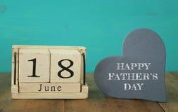 Calendario de madera del vintage el 18 de junio al lado del corazón de madera Fotos de archivo libres de regalías