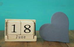 Calendario de madera del vintage el 18 de junio al lado del corazón de madera Fotografía de archivo libre de regalías
