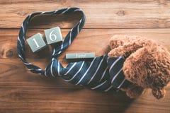 calendario de madera del vintage para el 16 de junio con el oso de peluche y la corbata ha Fotografía de archivo