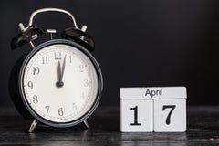 Calendario de madera de la forma del cubo para el 17 de abril con el reloj negro Foto de archivo libre de regalías
