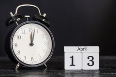 Calendario de madera de la forma del cubo para el 13 de abril con el reloj negro Imagen de archivo