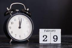 Calendario de madera de la forma del cubo para el 29 de febrero con el reloj negro Imágenes de archivo libres de regalías