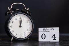 Calendario de madera de la forma del cubo para el 4 de febrero con el reloj negro Foto de archivo