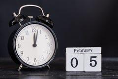 Calendario de madera de la forma del cubo para el 5 de febrero con el reloj negro Imágenes de archivo libres de regalías