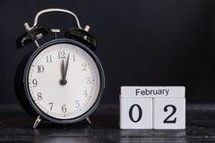Calendario de madera de la forma del cubo para el 2 de febrero con el reloj negro Fotografía de archivo