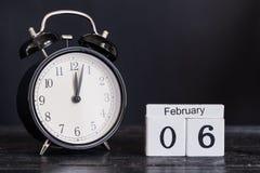 Calendario de madera de la forma del cubo para el 6 de febrero con el reloj negro Foto de archivo
