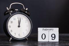 Calendario de madera de la forma del cubo para el 9 de febrero con el reloj negro Fotografía de archivo libre de regalías