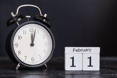 Calendario de madera de la forma del cubo para el 11 de febrero con el reloj negro Imagen de archivo libre de regalías