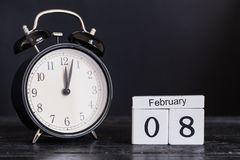 Calendario de madera de la forma del cubo para el 8 de febrero con el reloj negro Fotos de archivo libres de regalías