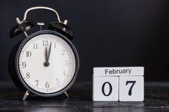 Calendario de madera de la forma del cubo para el 7 de febrero con el reloj negro Imagenes de archivo
