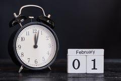 Calendario de madera de la forma del cubo para el 1 de febrero con el reloj negro Fotos de archivo libres de regalías