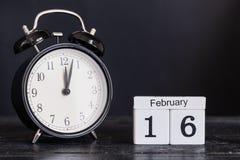 Calendario de madera de la forma del cubo para el 16 de febrero con el reloj negro Foto de archivo libre de regalías