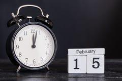 Calendario de madera de la forma del cubo para el 15 de febrero con el reloj negro Imágenes de archivo libres de regalías