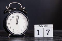 Calendario de madera de la forma del cubo para el 17 de febrero con el reloj negro Imagen de archivo libre de regalías