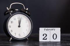 Calendario de madera de la forma del cubo para el 20 de febrero con el reloj negro Fotos de archivo libres de regalías