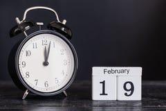 Calendario de madera de la forma del cubo para el 19 de febrero con el reloj negro Imagen de archivo libre de regalías