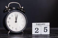 Calendario de madera de la forma del cubo para el 25 de febrero con el reloj negro Fotos de archivo