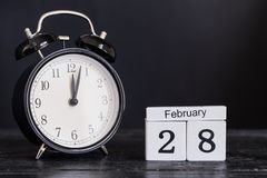 Calendario de madera de la forma del cubo para el 28 de febrero con el reloj negro Fotos de archivo