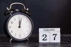 Calendario de madera de la forma del cubo para el 27 de febrero con el reloj negro Fotos de archivo libres de regalías