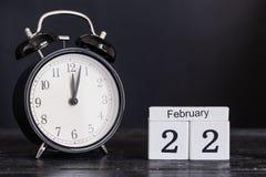 Calendario de madera de la forma del cubo para el 22 de febrero con el reloj negro Imagen de archivo libre de regalías