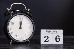Calendario de madera de la forma del cubo para el 26 de febrero con el reloj negro Imagen de archivo libre de regalías