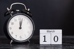 Calendario de madera de la forma del cubo para el 10 de marzo con el reloj negro Foto de archivo