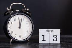Calendario de madera de la forma del cubo para el 13 de marzo con el reloj negro Foto de archivo libre de regalías